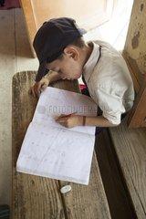 Schoolboy writing at his desk - Himalaya India