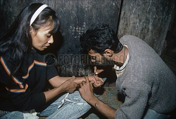 Drug addicts sharing needles to inject heroin Bombay India