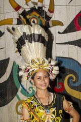 Woman wearing a traditional Dayak hat with Hornbill feathers