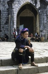 Black H'Mong woman sitting in front of a church Sapa Vietnam