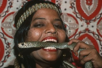 Girl snake charmer holding a Cobra in her mouth in India