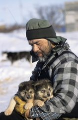 Man holding two Siberian pups of Husky Canada