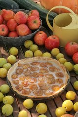 Tart with plum on a covered fruit table