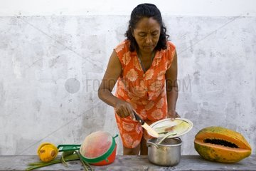 A woman prepares a variety of fruit juices with aloe vera