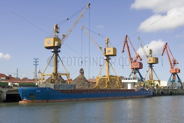 Unloading scrap metal from cargo ship into trucks Bilbao