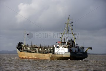Boat cleaning the channel of Kourou in French Guiana