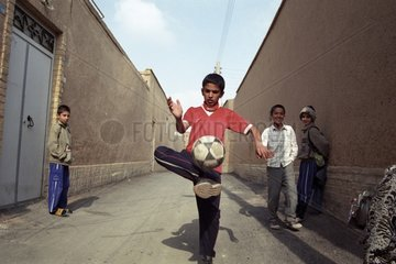 Boys iranniens playing football in the street