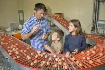 Farmer showing at his children eggs on the carpet