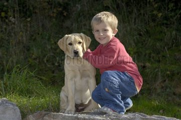 Young boy and his dog sit on a stone