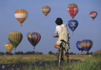Young cyclist watching hot air-ballons taking off Lorraine