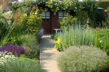 Allée fleurie menant à une maison de jardin Belgique