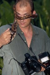 Photographer holding a snake firmly French Guiana