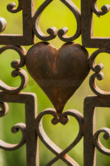 Heart on the iron cross of a tomb in the old cemetery of a small village in the Drome. France