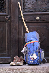 Backpack in front of the door of a cottage on which is hung a scallop shell emblem of pilgrims going to Santiago de Compostela  Saint Jean Pied de Port (64)  Pyrenees  France