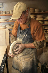 Potter modeling clay in a mold  Martine Gilles and Jaap Wieman  Village of Brantes  Provence  France