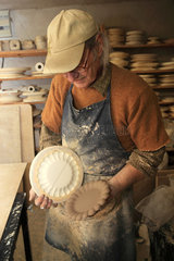 Potter unmolding a plate of a mold  Martine Gilles and Jaap Wieman  Village of Brantes  Provence  France