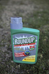 Glyphosate (Roundup) weed killer bottle in a garden  France