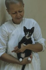 Nun carrying a kitten in its arms Kampuchea