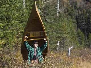 Philippe Henry carrying his canoe through the boreal forest