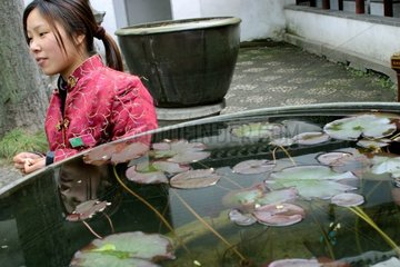 Girl close to the basin to the water lilies [AT]