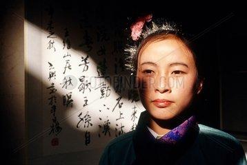 Pékin  jeune femme chinoise  devant des idéogrammes