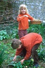 Enfants ramassant les oeufs de Pâques au jardin