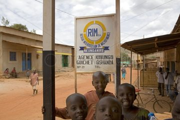 Children smiling in front of a panel of Micro finance Rwanda