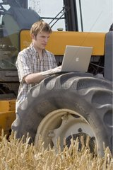 Young farmer using a laptop in the field France