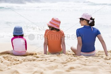 Girls sitting on a beach with UV protection t-shirts