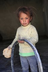 Girl playing with a wheel and eating one chapati India