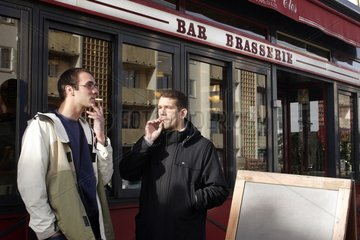 Men smoking their cigarettes outside of a brewery Paris