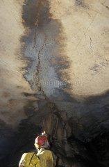 Speleologist under a concretioned way Ardèche France