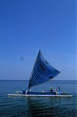Fisherman in its blue boat on Indian Ocean Bali