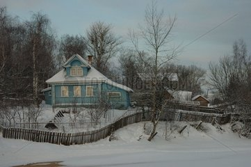 Traditional house at the edge of the cold river Russia