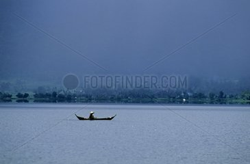 Fisherman in boat in the middle of Maninjau Lake Sumatra