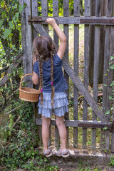 Girl trying to open the gate of a garden  summer  Moselle  France