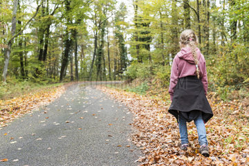 Girl walking in dead leaves on the edge of a forest road  autumn  Alsace  France