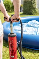 Woman inflating a freestanding pool in a garden  summer  Pas de Calais  France
