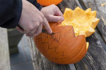 Little girls making a Halloween pumpkin