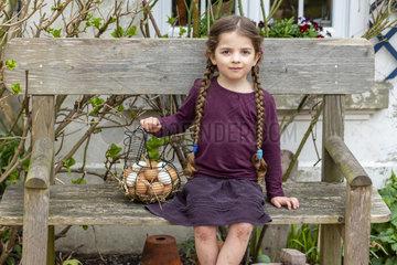 Girl carrying a basket full of chicken eggs in a garden