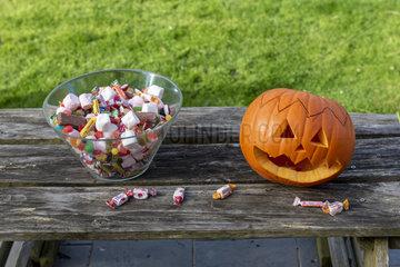 Little girls making a pumpkin for Halloween  jar of candy and pumpkin