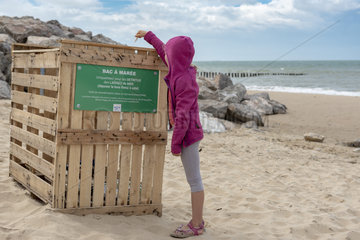 Girl throwing a plastic waste in a tidal bin on a beach on the Opal Coast  summer  Pas de Calais  France