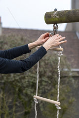 Woman hanging a rope ladder on a portico  in a garden  spring  Pas de Calais  France