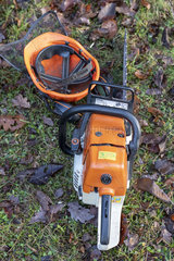 Chainsaw and helmet resting on the ground in winter  Moselle  France
