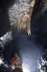 Speleologist observing stalactites in a cave France