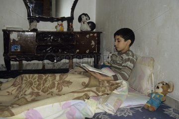 Boy irannien reading in his bed of 'fortune'