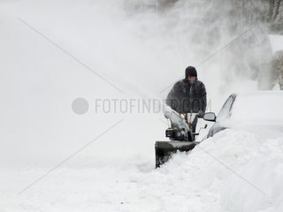 Man clearing the snow out of street after a snowstorm Quebec