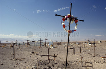 Peru  Cross with wreath in between many crosses on a catholic graveyard in a deserted landscape.