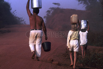 Amazon  Brazil. Settler family. Father and children carry buckets of water at Transamazonica road. Hard conditions of life. The Trans Amazonian highway. Toughness  hardness  work  housework  family work.