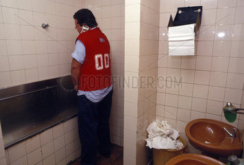 Daily life of stock exchange operator. Using the toilet and working on the telephone. Busy person  busy man  to urinate  bathroom  urinating  to piss  pissing  stress  stressing  no free time